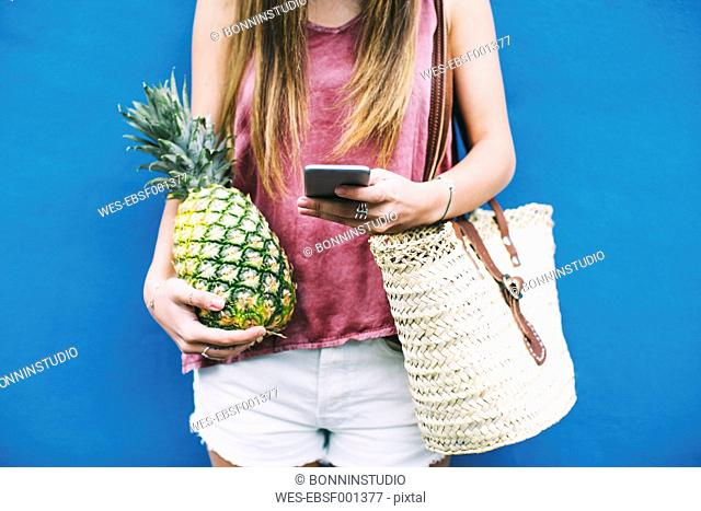 Young woman standing with beach bag, cell phone and pineapple