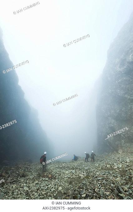 Walkers descending The Great Stone Chute in the mist, from near the top of Sgurr Alasdair, Black Cuillin; Isle of Skye, Scotland