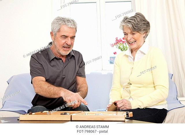 A senior man and a senior woman playing backgammon