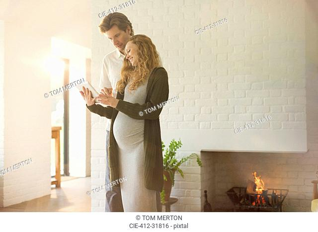 Pregnant couple using digital tablet near fireplace in living room