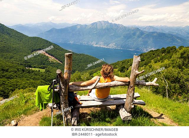 Woman taking a break on a wooden bench while hiking on Monte Gambarogno on lake Lago Maggiore, Ticino, Switzerland, Europe