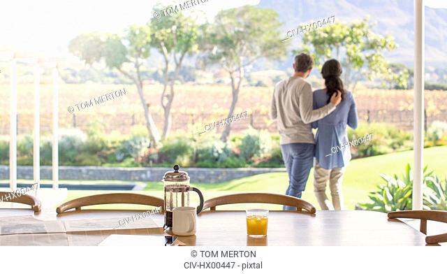 Couple hugging on patio overlooking field