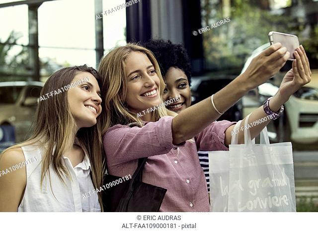 Friends using smartphone to take a selfie while out shopping