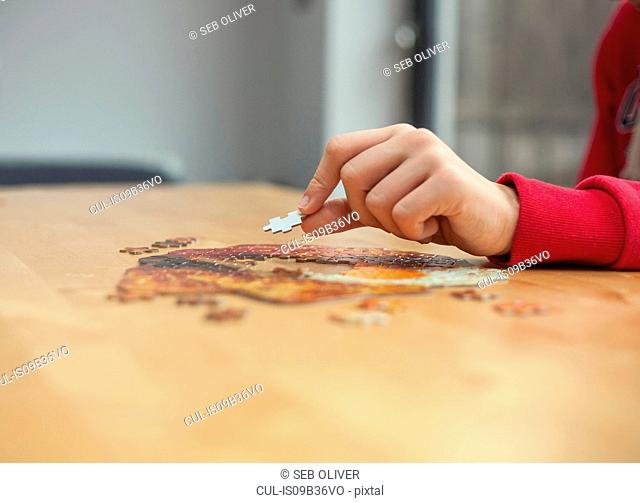 Boy's hand placing jigsaw piece on jigsaw puzzle at table