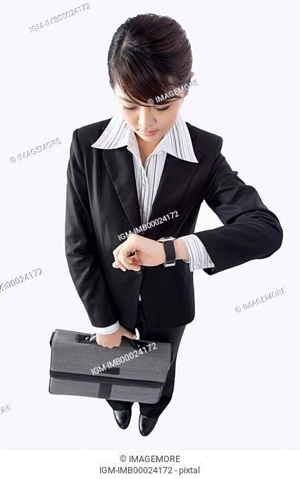 Young business woman holding briefcase and reading the time