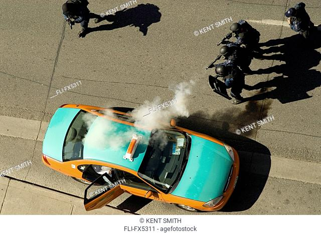 Police SWAT team, Wearing gas masks, Firing Tear Gas into Taxi, on Bloor Street, Toronto, Ontario