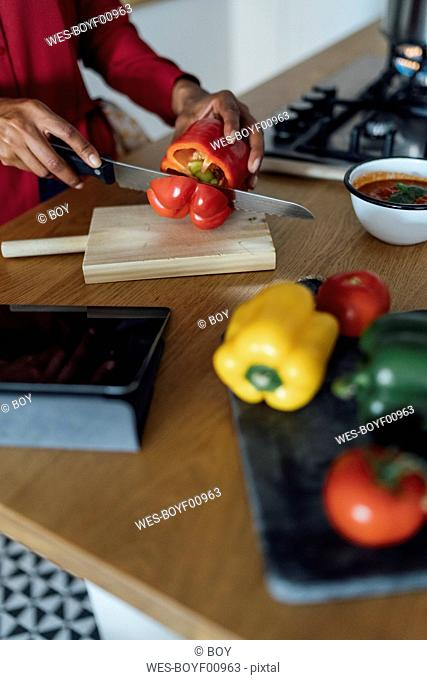 Hands of a woman, chopping bell peppers on a chopping board