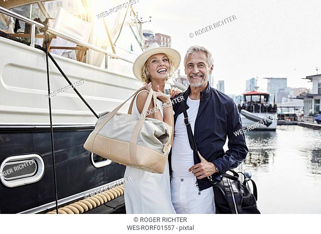 Older man and young woman standing with travelling bags on jetty next to yacht