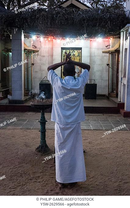 Man worshipping at a shrine in the Sacred Precinct of the pilgrimage town of Kataragama, Sri Lanka