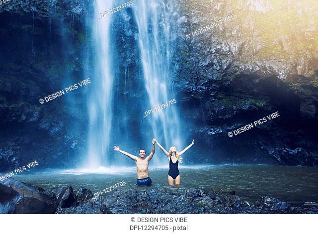 Couple enjoying pool at the base of large waterfall in Hawaii