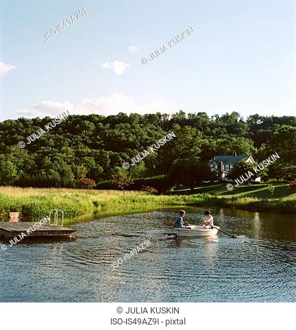 Mother and daughter in rowing boat, on water