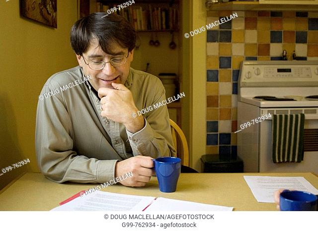 Canada, Ontario, Kitchener. Joe Manicini, founder and director of The Working Centre, reading papers and drinking coffe in the kitchen of his home