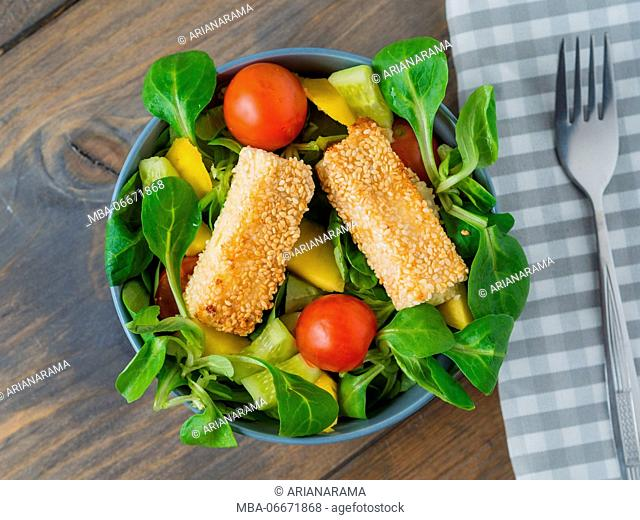 Baked feta cheese in sesame crust on mixed salad with mango