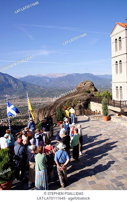 Clifftop monasteries. Varlaam monastery. Courtyard. Group of people. Tourists. Building. View to valley. Mountains