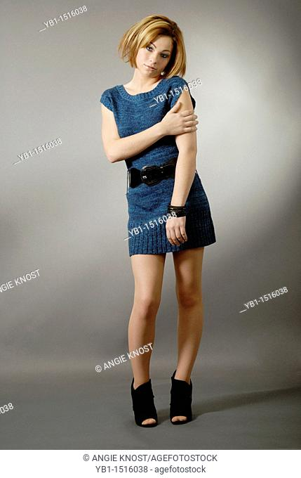 Fashion image of a teenager girl wearing a sweater-dress, she has a trendy, short hairstyle with color highlights