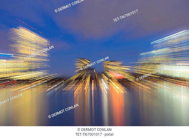 Light trails from city skyline at dusk