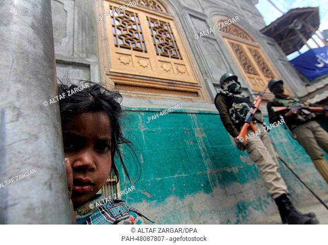 Srinagar, Kashmir ,India . A Kashmiri young girl stands on the road as an Indian paramilitary soldiers stand guard during an election campaign rally at down...