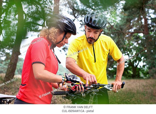 Mountain biking couple checking cycle handlebar in forest
