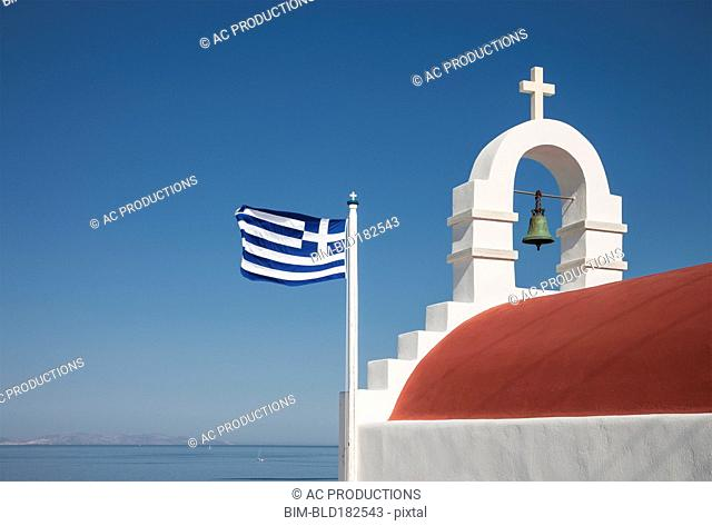 Greek flag and bell arch under blue sky