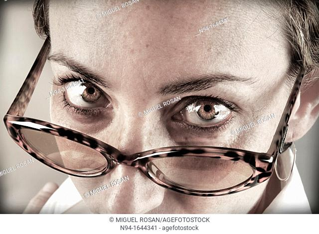 Closeup of young woman staring at the camera above his glasses