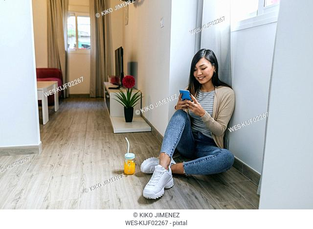 Young woman sitting on floor, using smartphone
