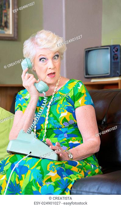 One surprised woman in conversation rotary telephone