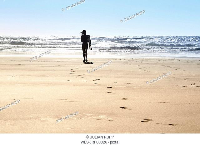 Portugal, Algarve, man on the beach with surfboard