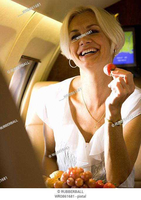 A businesswoman eating fruit and laughing in an airplane