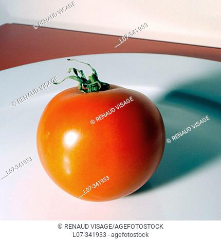 Red tomato on white plate
