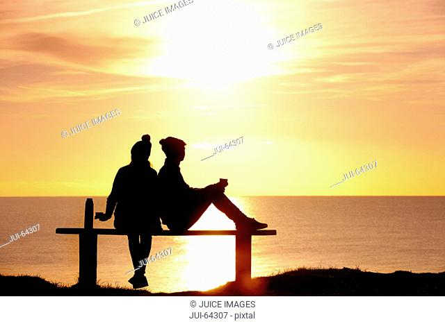 Silhouette of couple, sitting on bench and drinking tea from thermos, against sunset over the ocean