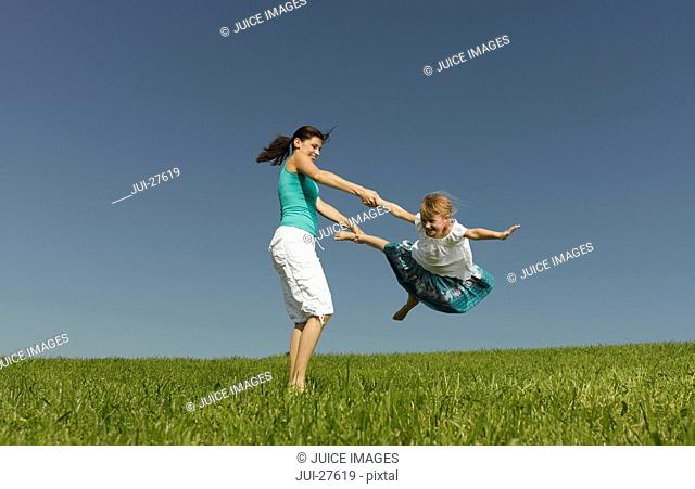Mother swinging her daughter through the air