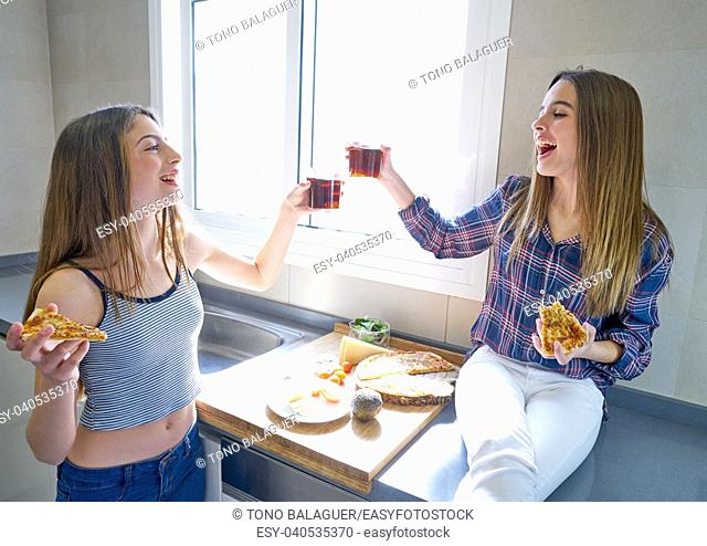 best friend teen girls eating pizza in the kitchen at lunch having fun
