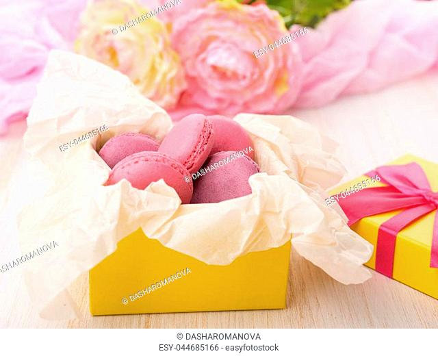 Sweet cakes in a yellow box on a wooden table. Pink flowers