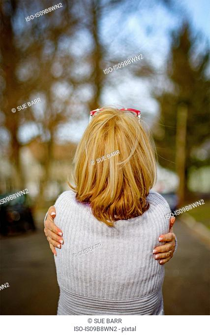 Rear view of mature in park hugging herself