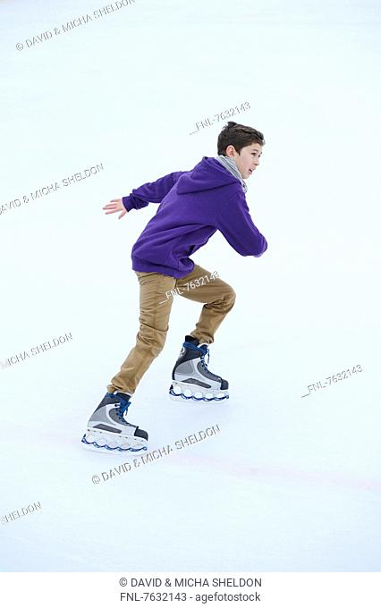 Boy ice-skating on a frozen lake