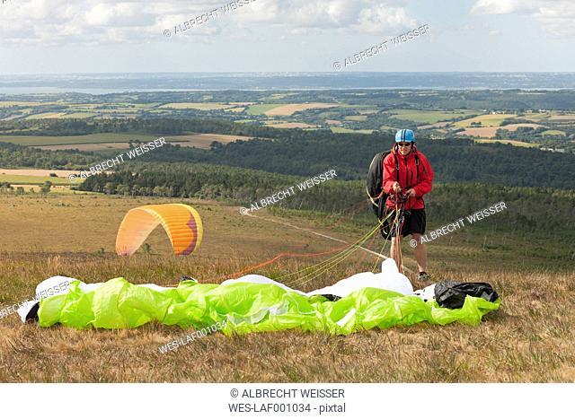France, Bretagne, Finistere, man packing his paraglider