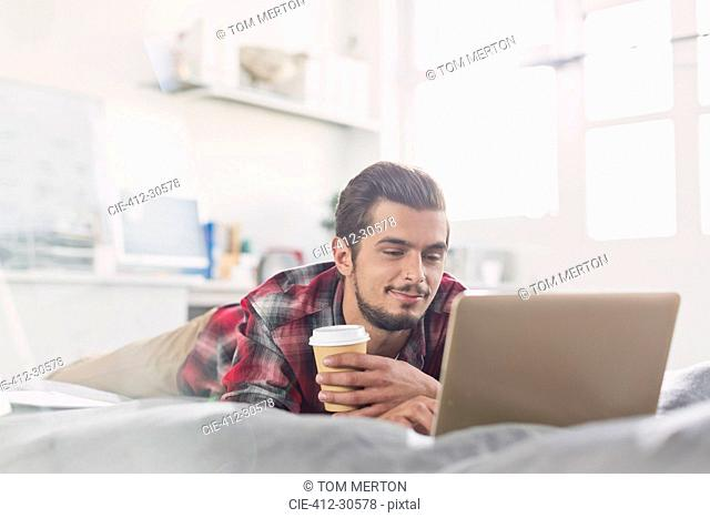 Young man drinking coffee at laptop on bed