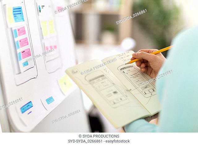 ui designer with user interface sketch in notebook