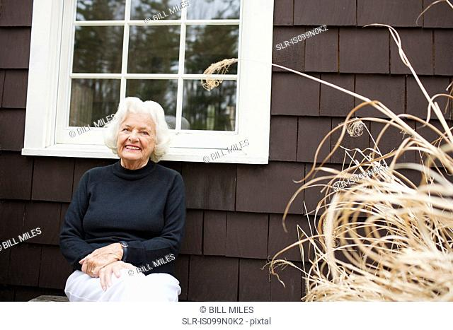 Portrait of senior woman outside house