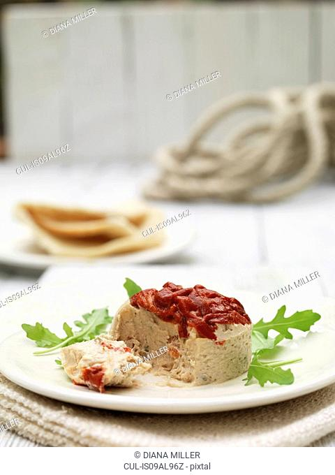 Plate of tuna terrine and roasted red peppers with pita bread and rocket garnish