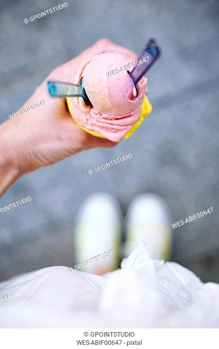 Woman's hand holding ice cream cone with two scoops and spoons