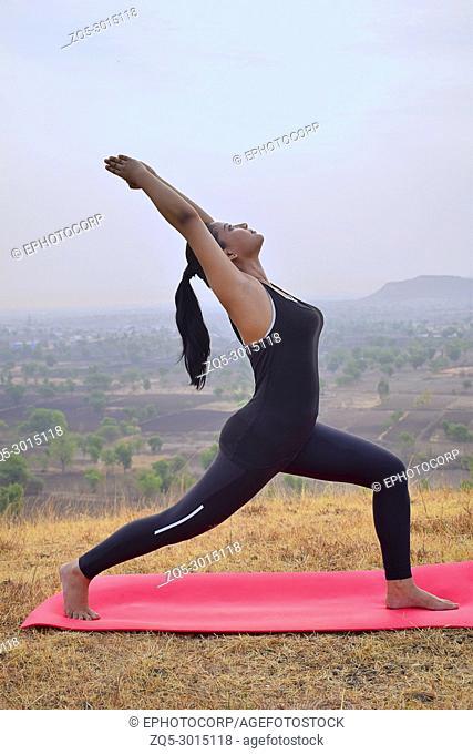 Young Indian girl doing Yoga . Surya Namaskar with mountain backdrop Pune, Maharashtra