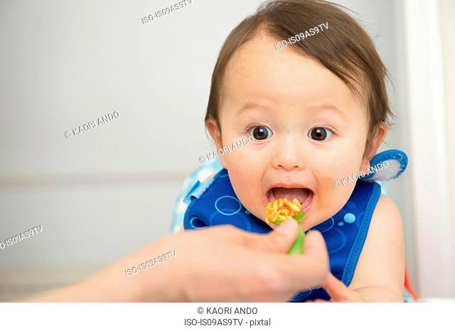 Hand of mother feeding baby food to open mouthed son in kitchen