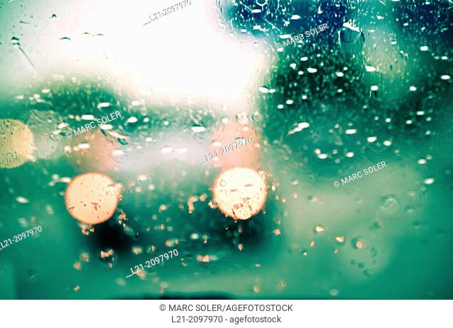 Rain drops on windshield. Blurred view of cars