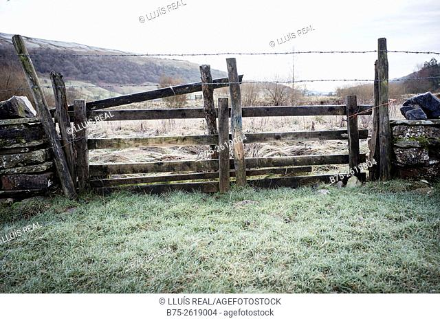 Sunrise in the wetlands on the banks of river Wharfe in a cold winter day with a wooden barrier in the foreground. Buckden, Skipton, Yorkshire Dales, England