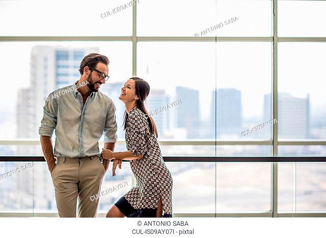 Couple talking in front of hotel room window, Dubai, United Arab Emirates