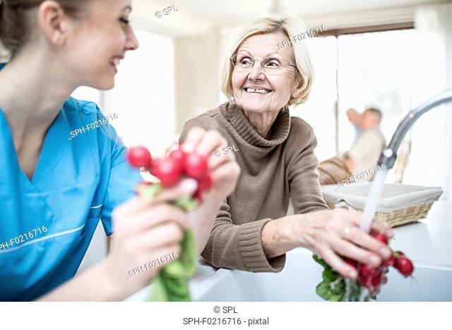 Carer washing radishes with woman