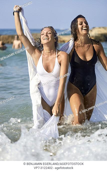 two lively women in white blanket sheet, playful, happiness, dancing in sea, best friends, friendship goals, holidays, adventure, water, splashes