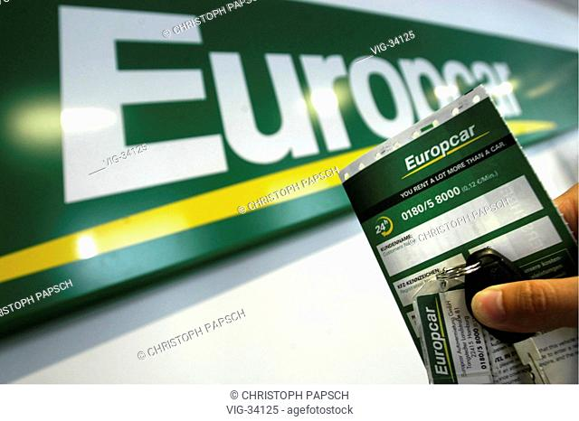 Car key withe Europcar Keychain and Customer Documentation in front of the Europcar logo. - BONN, GERMANY, 11/06/2003