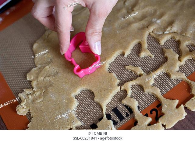 Cutting out of the rolled dough the animal shaped shortbreads with a biscuit cutter